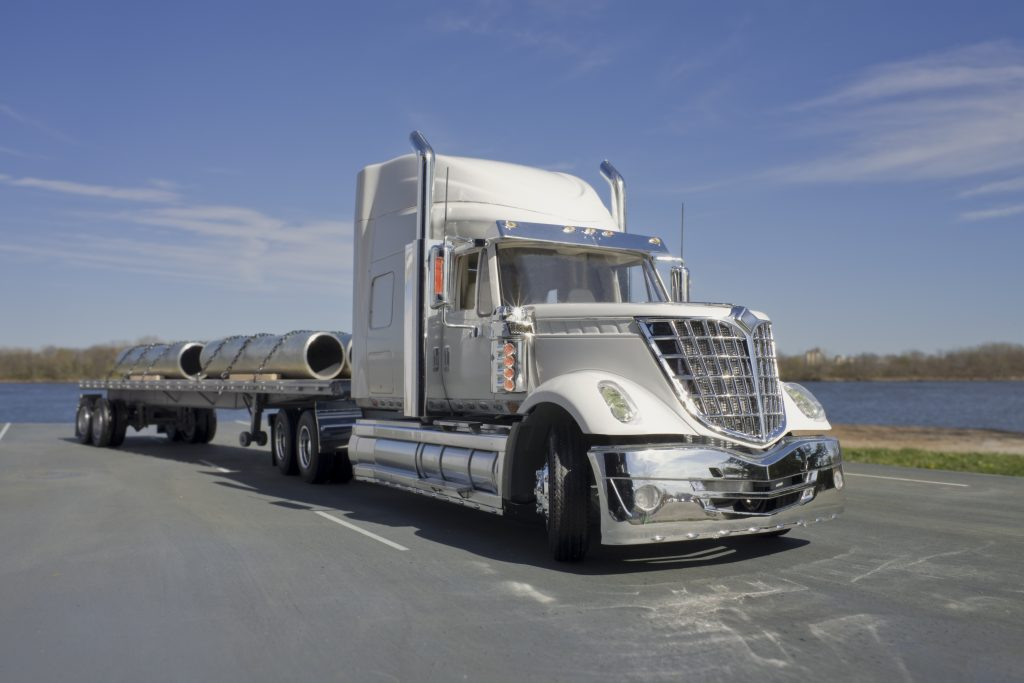 This is a photograph of a model semi type truck with flatbed trailer. It is hauling a load of steel pipe.