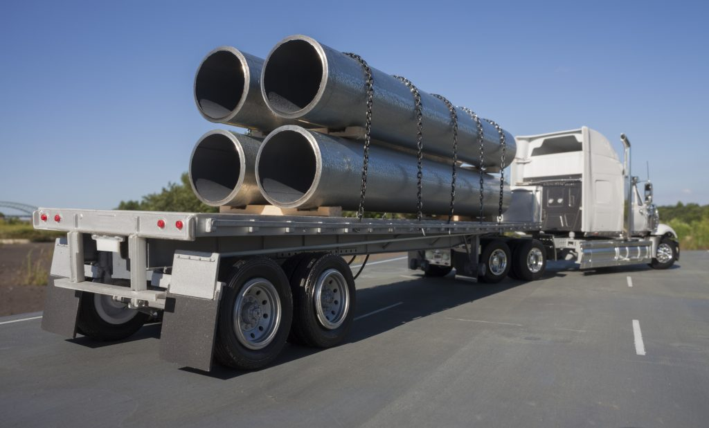 This is a photograph of a model flatbed truck hauling a load of large steel pipe.